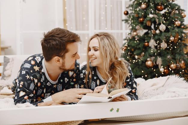 Menschen in einer christman-dekoration. mann und frau in einem identischen pyjama. familie auf einem bett.