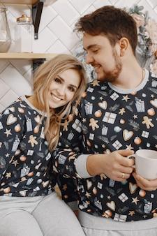 Menschen in einer christman-dekoration. mann und frau in einem identischen pyjama. familie in einer küche.
