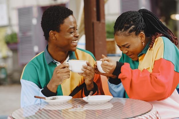Menschen in identischer kleidung. afrikanisches paar in der herbststadt. leute am tisch.