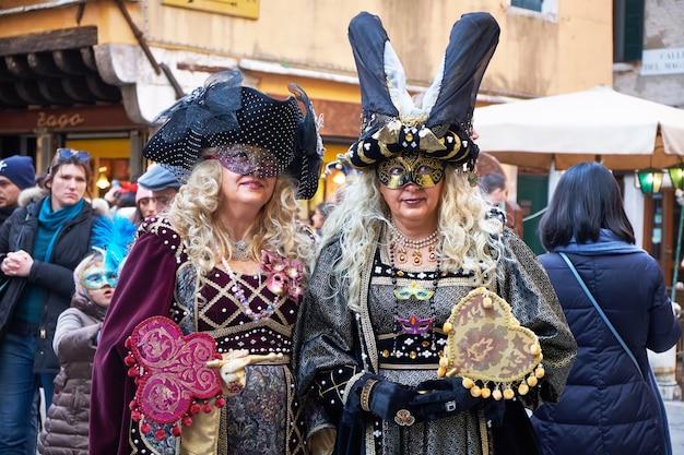 Menschen in masken und kostümen beim karneval in venedig