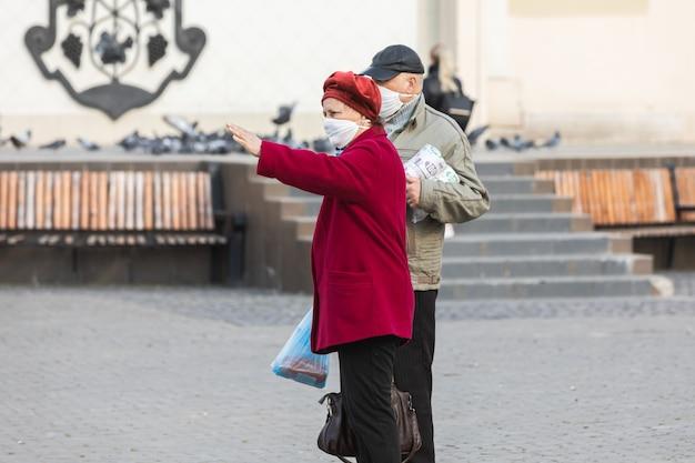 Menschen in medizinischen masken auf der straße eilen während der coronavirus-epidemie über ihr geschäft. älteres glückliches paar