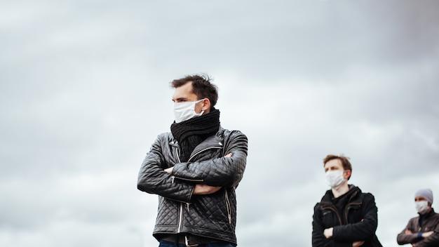 Menschen in schutzmasken, die in sicherem abstand stehen. konzept des gesundheitsschutzes