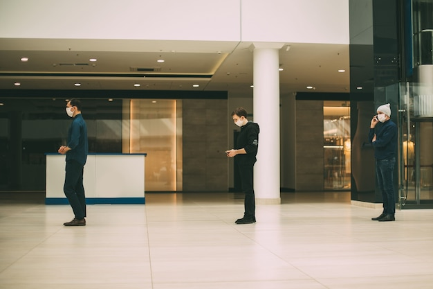 Menschen in schutzmasken stehen in einer schlange und halten abstand. foto mit einem kopierraum