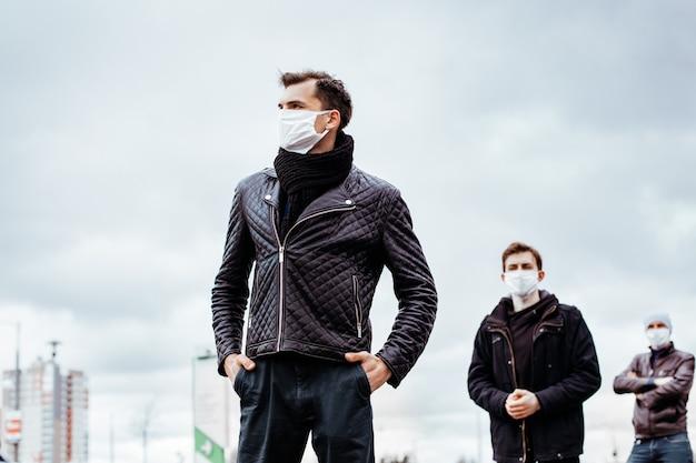 Menschen in schutzmasken stehen in sicherer entfernung. konzept des gesundheitsschutzes