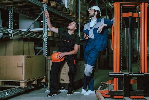 Menschen in uniform und schutzhelmen in der pause bei der arbeit