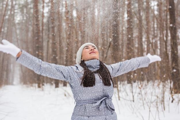 Menschen-, jahreszeit- und naturkonzept - attraktive frau im grauen mantel, die spazieren geht und spaß im winter hat
