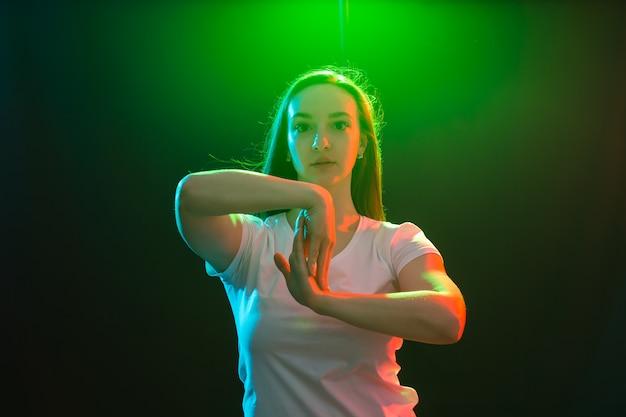 Menschen, jazz-funk- und tanzkonzept - junge frau tanzt in der dunkelheit und hält eine hand in der nähe ihres gesichts.