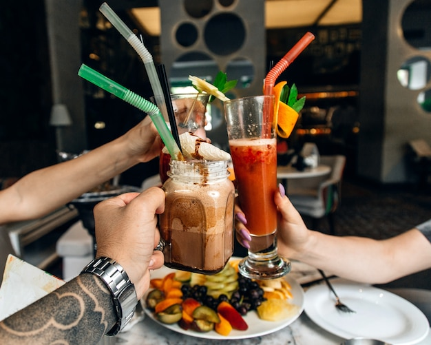 Menschen jubeln mit verschiedenen cocktails