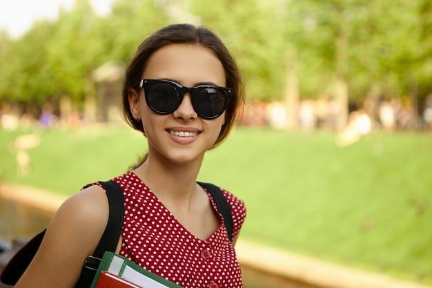Menschen-, jugend-, schul- und bildungskonzept. modisches glückliches positives college-mädchen, das schwarze sonnenbrillen trägt und rucksack trägt, schönes sommerwetter genießt, vom unterricht nach hause geht,