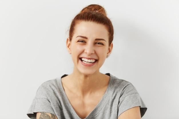 Menschen, jugend und glück. porträt der schönen glücklichen kaukasischen teenager-frau, die lässig breit lächelnd gekleidet trägt, ihre perfekten weißen zähne zeigt, freizeit genießt, wochenende drinnen verbringt