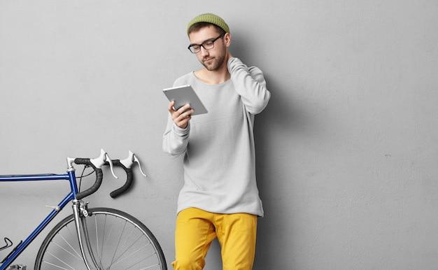 Menschen, jugendliche, moderne technologien und lifestyle-konzept. kluger männlicher student, der eine brille trägt, zur universität oder zum college geht, vor der prüfung material in tablette liest und überarbeitet, was er gelernt hat