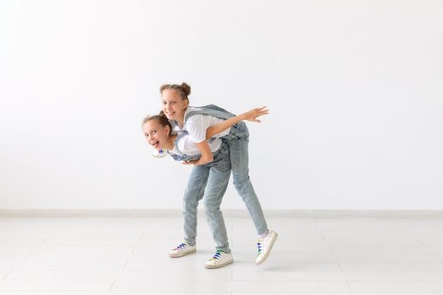 Menschen, kinder und familienkonzept - kleines mädchen, das ihre zwillingsschwester huckepack auf weißem hintergrund trägt.