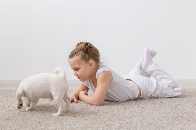 Menschen kinder und haustiere konzept kleines kind mädchen auf dem boden mit niedlichen welpen jack russell liegen