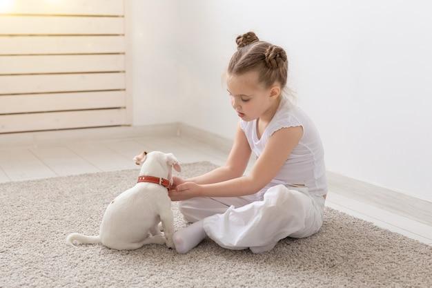Menschen, kinder und haustiere konzept - kleines kind mädchen sitzen auf dem boden mit niedlichen welpen jack russell terrier und spielen