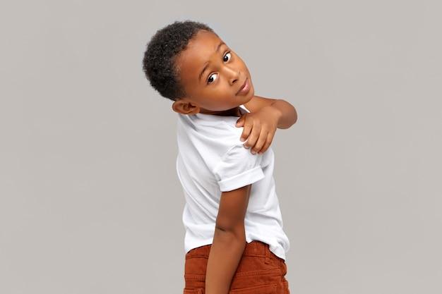 Menschen, kindheit, spaß, freizeit und lifestyle-konzept. netter entzückender afroamerikanischer kleiner junge in der freizeitkleidung, die mit dem drehenden kopf steht und freudigen glücklichen gesichtsausdruck hat