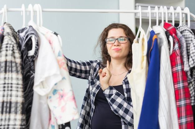 Menschen, kleidung und einkaufskonzept - porträt einer hübschen frau, die durch den kleiderschrank schaut