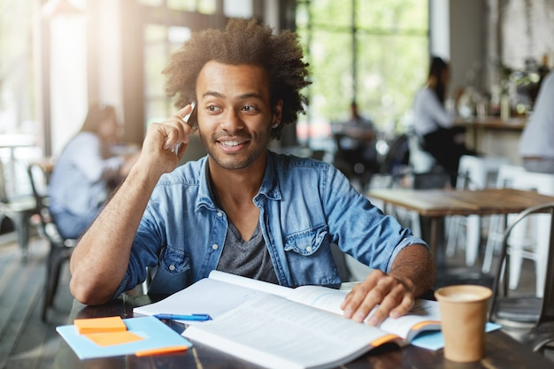 Menschen, lebensstil, bildung und modernes technologiekonzept. ehrliche aufnahme eines fröhlichen afroamerikanischen männlichen studenten in stilvoller kleidung, der eine nette unterhaltung auf dem handy genießt, während er hausaufgaben in der kantine macht
