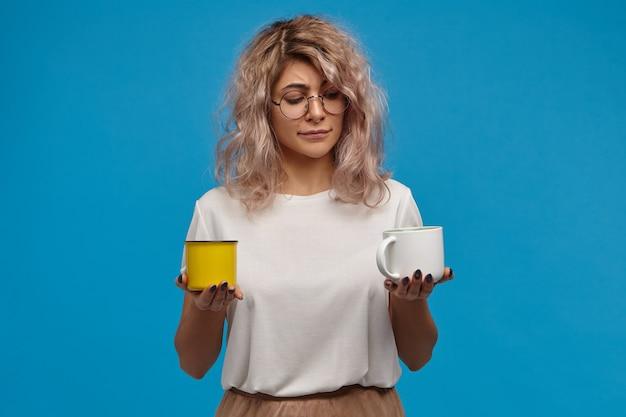 Menschen, lebensstil, getränke- und lebensmittelkonzept. lustige unentschlossene zweifelhafte junge frau mit unordentlichem rosafarbenem haar, das dilemma gegenübersteht und zögert, während sie zwischen kaffee und tee wählt