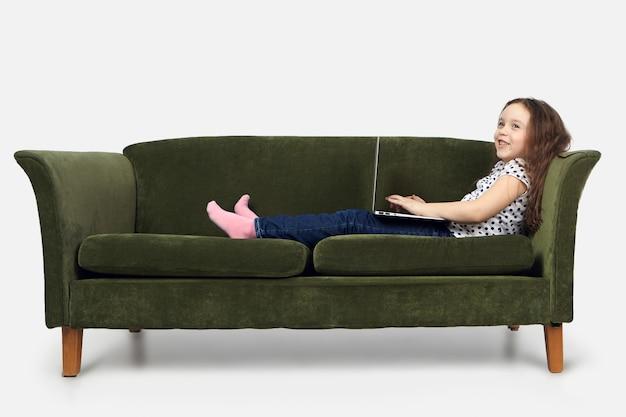 Menschen, lebensstil, kindheit und modernes technologiekonzept. hübsches schulmädchen, das sich zu hause mit laptop nach dem unterricht in der schule entspannt, cartoons oder videoblog ansieht und mit einem glücklichen lächeln wegschaut