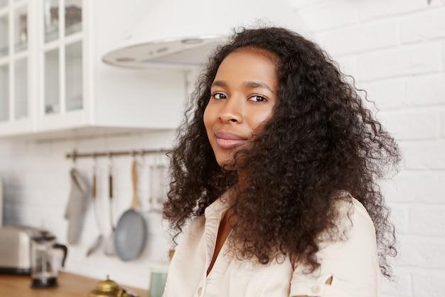 Menschen, lebensstil, kochen und lebensmittelkonzept. innenaufnahme der niedlichen stilvollen jungen dunkelhäutigen hausfrau mit dem lockigen haar, das auf ehemann von der arbeit wartet, abendessen in der küche macht und schaut