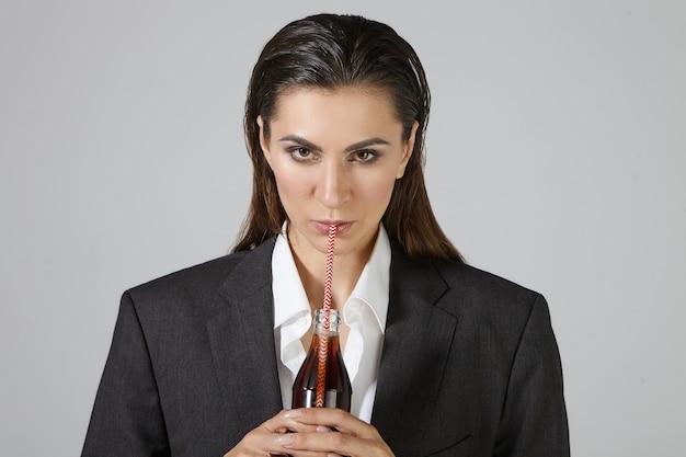 Menschen, lebensstil, lebensmittel- und getränkekonzept. bild der ernsthaften durstigen geschäftsfrau gekleidet in übergroßen männerkleidern, die isolierte haltende glasflasche darstellen, braunes soda gedankenstroh nippend