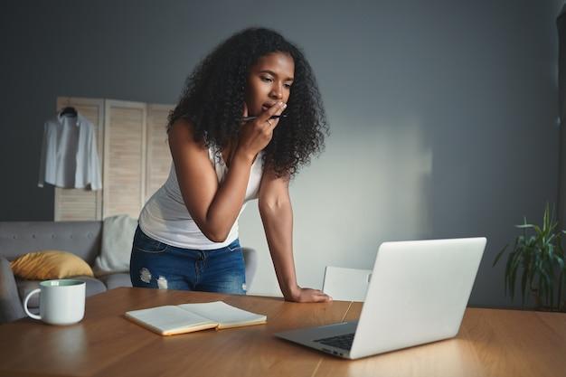 Menschen, lebensstil, moderne technologie, berufs- und berufskonzept. porträt der schönen jungen afrikanischen schriftstellerin, die sich besorgt fühlt, kreative blockade erlebt, laptop benutzt und notizen macht