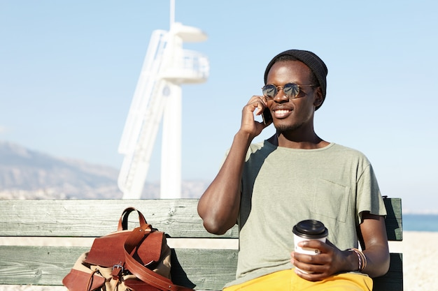 Menschen, lebensstil, reisen, tourismus, sommer und urlaubskonzept. hübscher modischer junger afroamerikanischer mannreisender, der auf hölzerner bank am meer mit kaffee zum mitnehmen sitzt und am telefon spricht