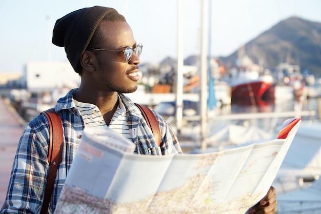 Menschen, lebensstil, reisen und abenteuer konzept. mann am kai, umgeben von yachten und schiffen in modischer hut- und spiegelsonnenbrille, die papierführer hält, der mit erfreutem lächeln zur see schaut