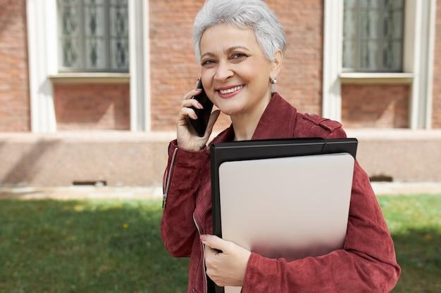 Menschen, lebensstil, technologie und kommunikationskonzept. porträt der fröhlichen stilvollen geschäftsdame mittleren alters, die auf handy spricht