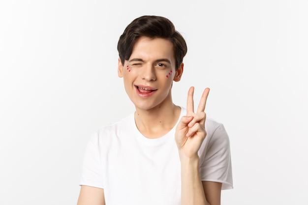Menschen, lgbtq community und lifestyle-konzept. glücklicher und niedlicher schwuler mann mit glitzer auf gesicht, friedenszeichen zeigend und lächelnd, stolzfeiertag, weißer hintergrund feierend.