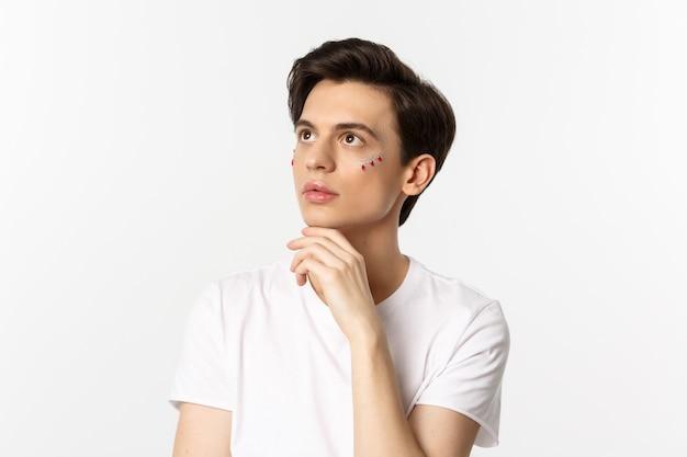 Menschen, lgbtq community und lifestyle-konzept. schöner androgyner mann mit glitzer im gesicht, der die obere linke ecke sinnlich betrachtet und über weiß steht.