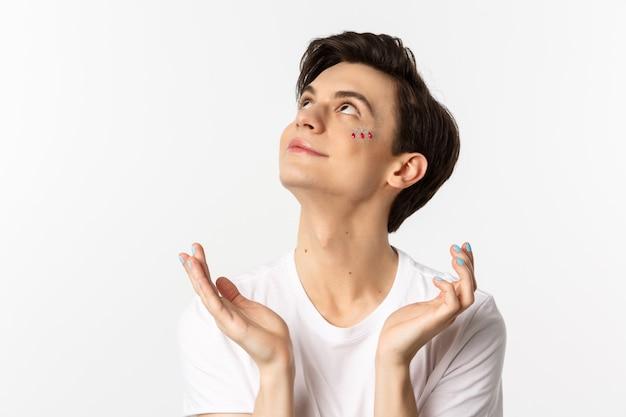 Menschen, lgbtq und schönheitskonzept. nahaufnahme des hübschen androgynen mannes mit glitzer auf gesicht und polierten fingernägeln, träumerisch aussehend und lächelnd, weiß.