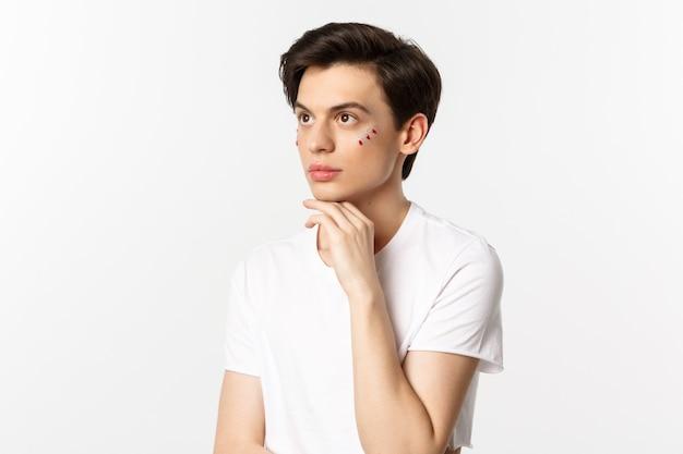 Menschen, lgbtq und schönheitskonzept. schöner androgyner mann mit glitzer unter den augen, blick auf die obere linke ecke, posierend gegen weiß.