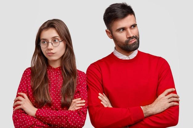 Menschen, liebe und missverständnis konzept. foto des unzufriedenen paares mit verschränkten armen, kämpfen, rote kleidung tragen