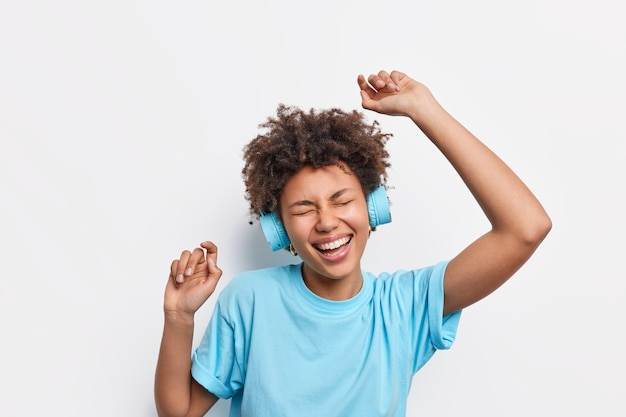 Menschen lifestyle-freizeitkonzept. energiegeladene, fröhliche afroamerikanerin mit lockigem haar tanzt unbeschwert hebt die arme, fühlt sich amüsiert genießt lieblingsmusik trägt drahtlose kopfhörer blaues t-shirt