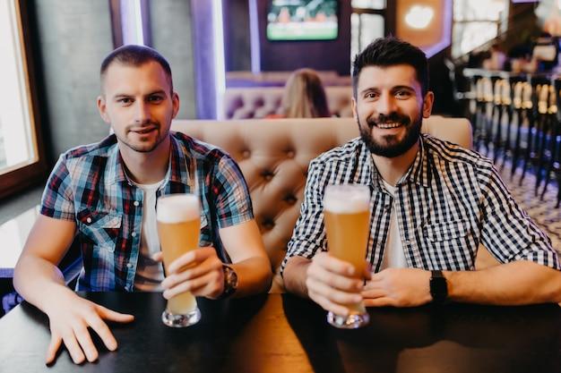 Menschen-, männer-, freizeit-, freundschafts- und feierkonzept - glückliche männliche freunde, die bier trinken und gläser an der bar oder im pub klirren