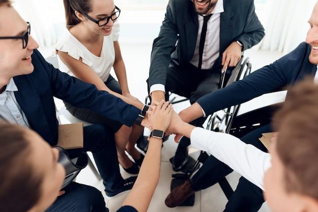 Menschen mit behinderungen legen die hände zusammen.