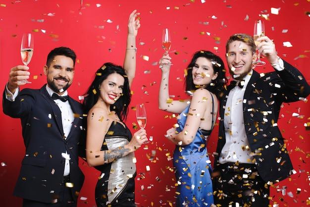 Menschen mit champagner stehen unter konfetti
