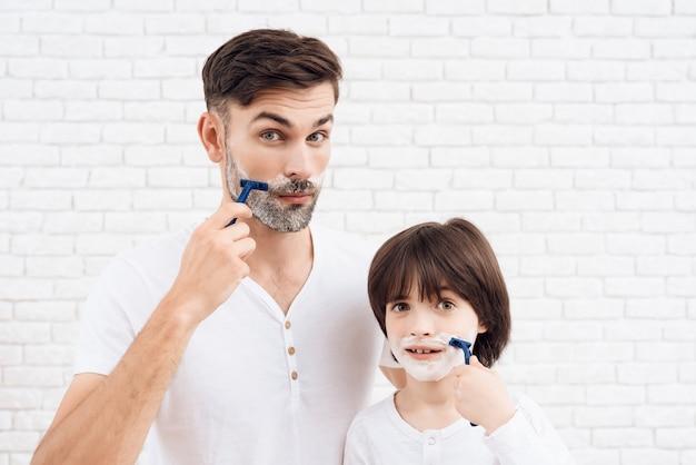Menschen mit dunklen haaren lernen sich zu rasieren.