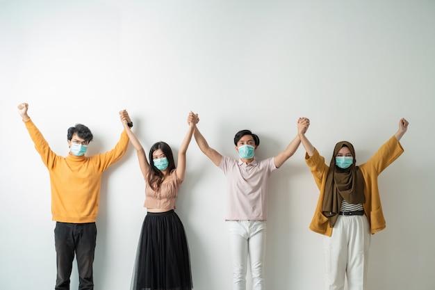 Menschen mit gesichtsmasken halten hand