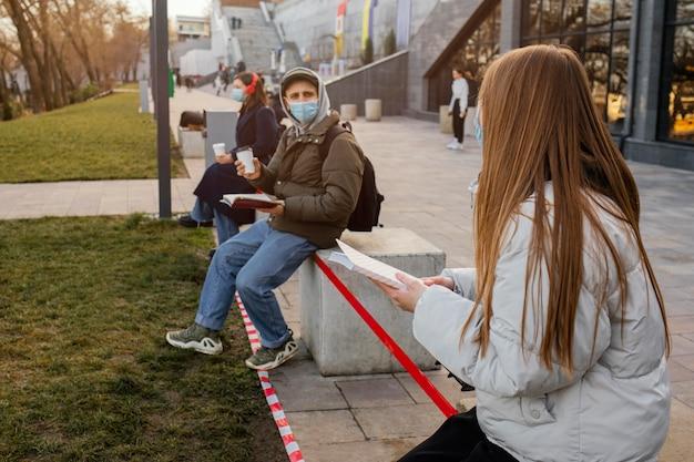 Menschen mit maske in abstand voneinander