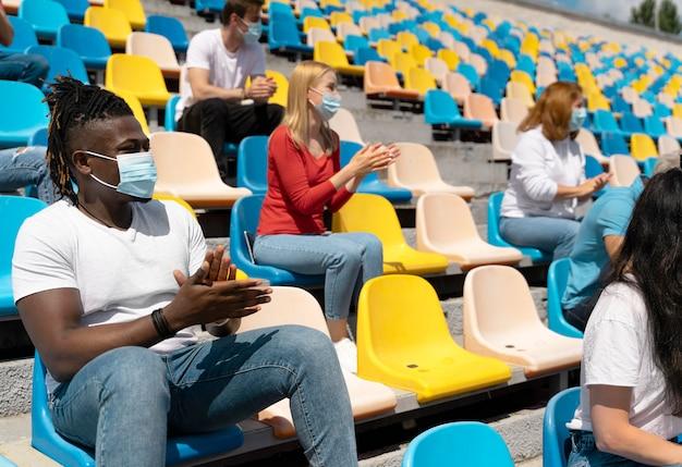 Menschen mit medizinischen masken, die ein spiel betrachten