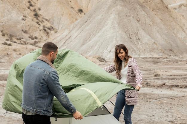 Menschen mit mittlerem schuss, die ein zelt aufbauen