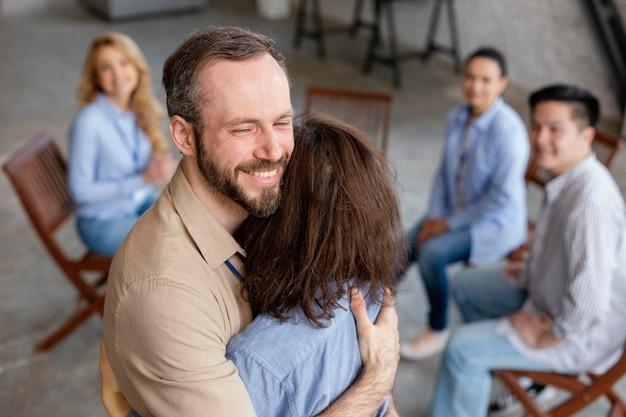 Menschen mit mittlerem schuss, die sich in der therapie umarmen