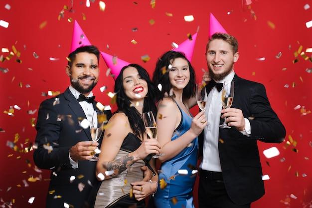Menschen mit partyhüten und champagner unter konfetti
