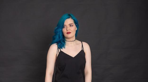 Menschen-, mode- und haarkonzept - porträt einer jungen frau mit blauen haaren im schwarzen kleid mit blauen haaren auf schwarzem hintergrund mit kopierraum