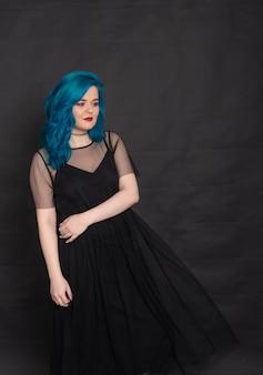 Menschen-, mode- und haarkonzept - porträt einer jungen frau mit blauen haaren im schwarzen kleid mit blauen haaren auf schwarzem hintergrund