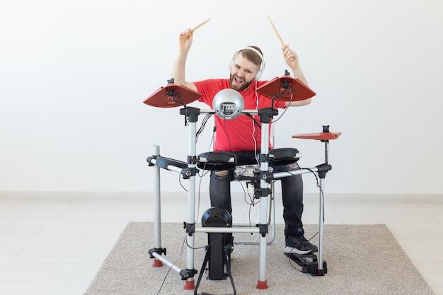 Menschen-, musik- und hobbykonzept - mann in rotem t-shirt, der auf dem elektronischen schlagzeug spielt.