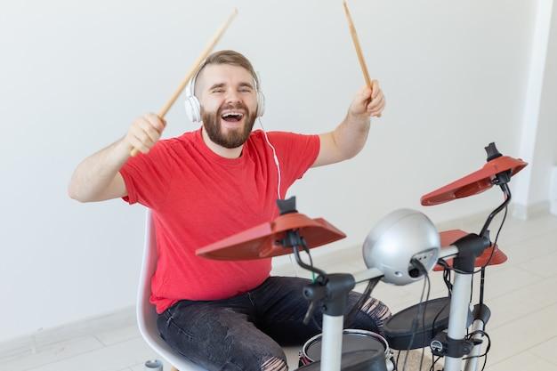 Menschen-, musik- und hobbykonzept - mann mit weißen kopfhörern, die schlagzeug auf hellem hintergrund spielen.