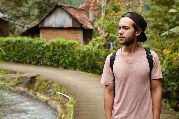 Menschen, natur und sommerkonzept. stilvoller junger unrasierter hipster-mann, der hysterese und rucksack trägt, die draußen im freien beim gehen entlang der landstraße im ländlichen bereich entspannen